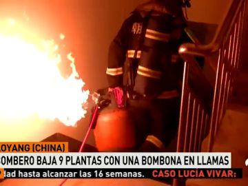 Un bombero baja nueve pisos de un edificio con una bombona en llamas