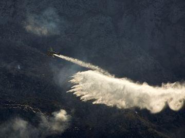 Una avioneta trabaja en las labores de extinción del incendio forestal declarado en el Montgó