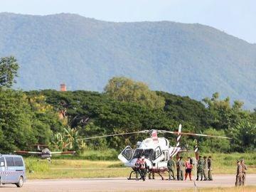 Soldados y policías tailandeses evacúan en helicóptero a uno de los niños rescatados