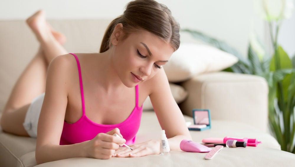 Chica pintándose las uñas