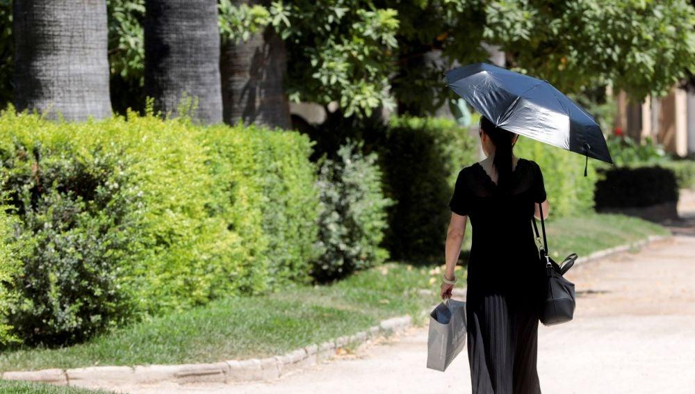 Una mujer se protege con un parasol