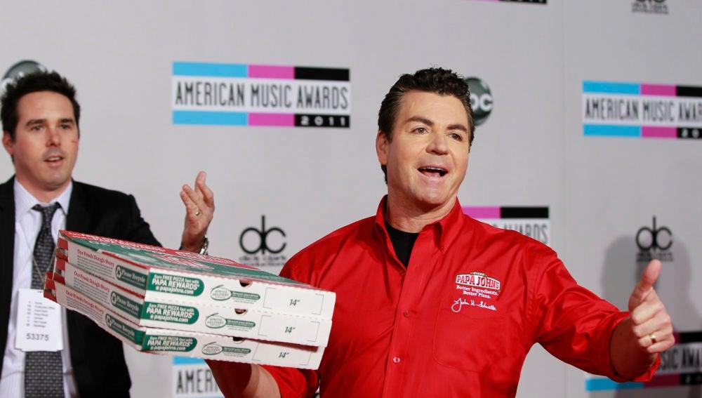 John Schnatter con pizzas de la compañía