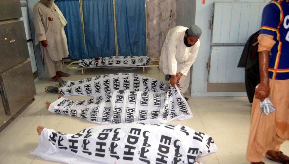 Un hombre cubre los cuerpos de las víctimas del atentado bomba