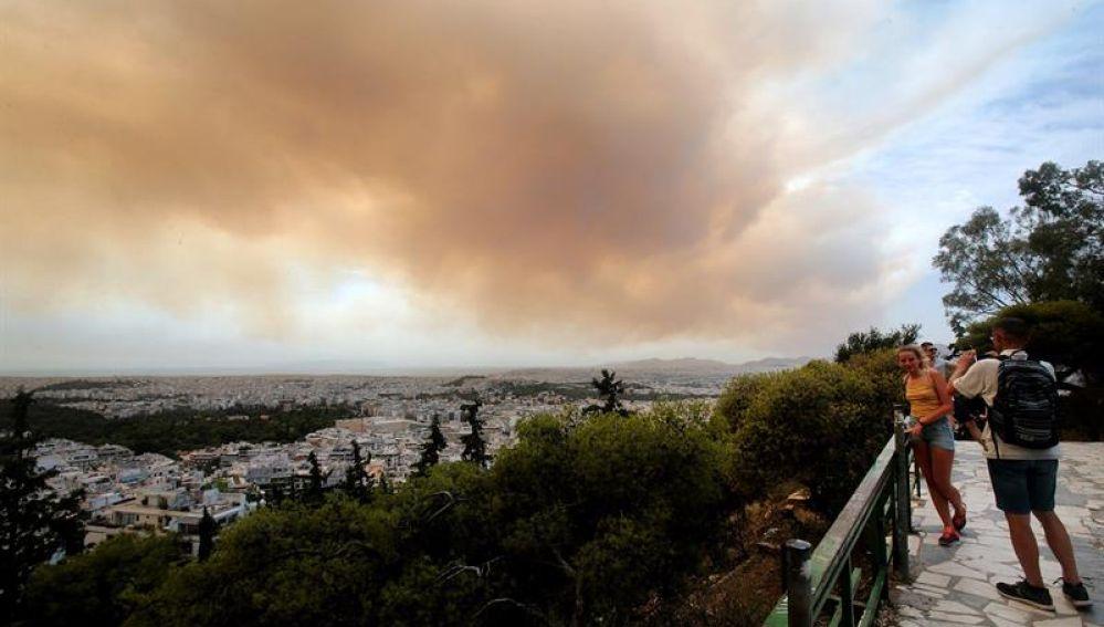 Unos turistas fotografían las nubes densas de humo que se expanden en el cielo debido un incendio en las montañas de Gerania, a 54 km de Atenas
