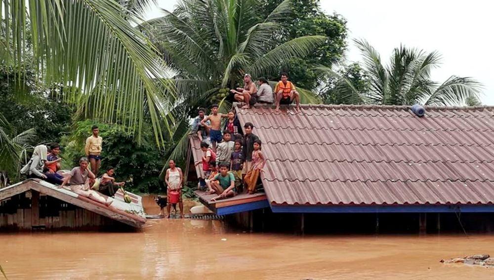 Un grupo de personas aguarda en lo alto de un tejado en una zona inundada tras el derrumbe de una presa hidroeléctrica en un pueblo cercano a la provincia de Attapeu, en Laos.