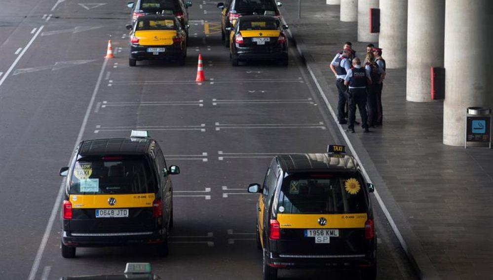 Un grupo de taxistas permanecen parados con sus vehículos en el Aeropuerto de Barcelona