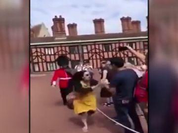 Un guardia real británico empuja a una turista que se había saltado el cordón de seguridad de Windsor