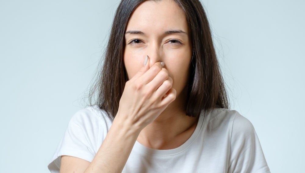 Mujer tapándose nariz
