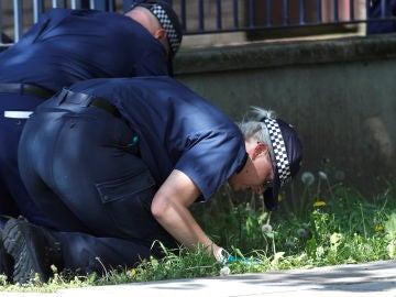Policías británicos buscando pruebas sobre la escena de un crimen