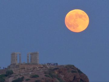 Una luna llena se levanta durante un eclipse lunar detrás de la estatua de la antigua diosa Atenea en Atenas
