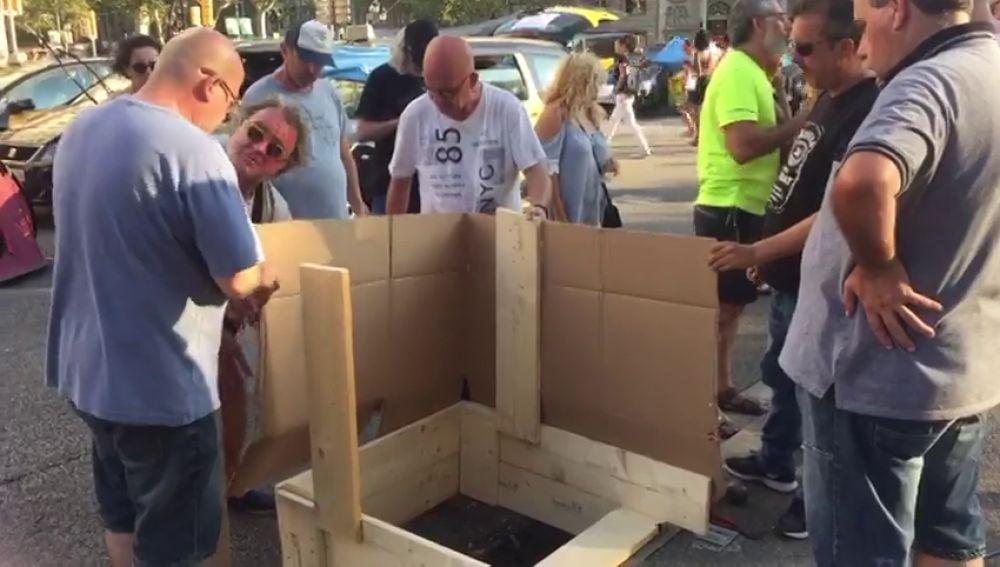 Los taxistas de Barcelona construyen un baño en la Gran Vía que mantienen cortada