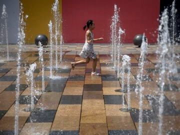 A child plays in a fountain in the Sanlitun area of Beijing, China