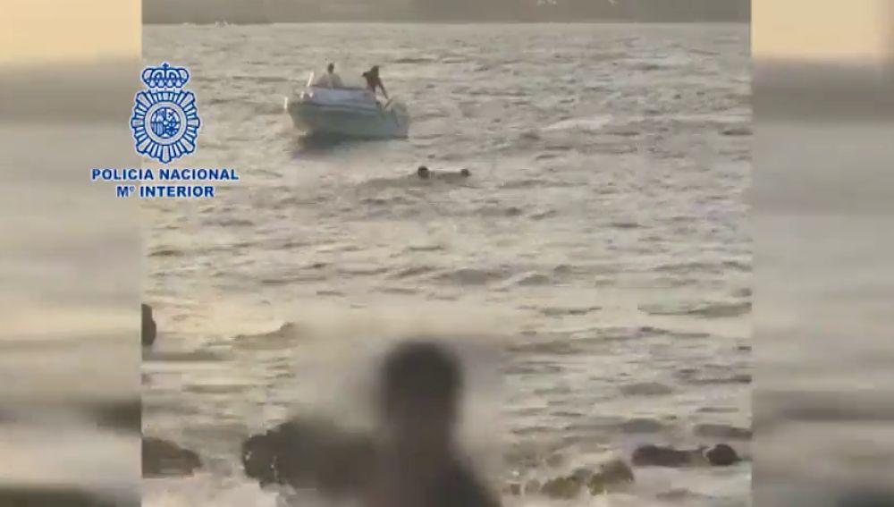 Un policía rescata a un migrante que saltó al mar en la bahía de Algeciras