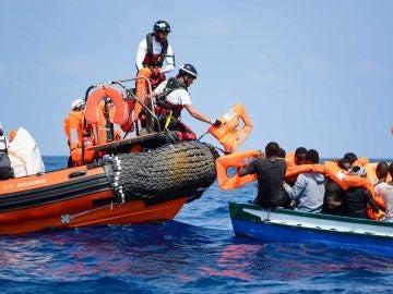 Varios migrantes siendo rescatados para ser llevados abordo del barco de rescate Aquarius.