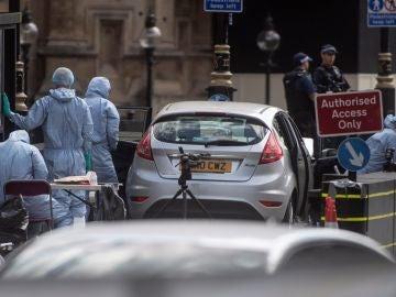 Oficiales forenses examinan el coche que chocó contra las barreras del Parlamento británico