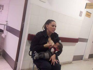 La policía dando el pecho al bebé