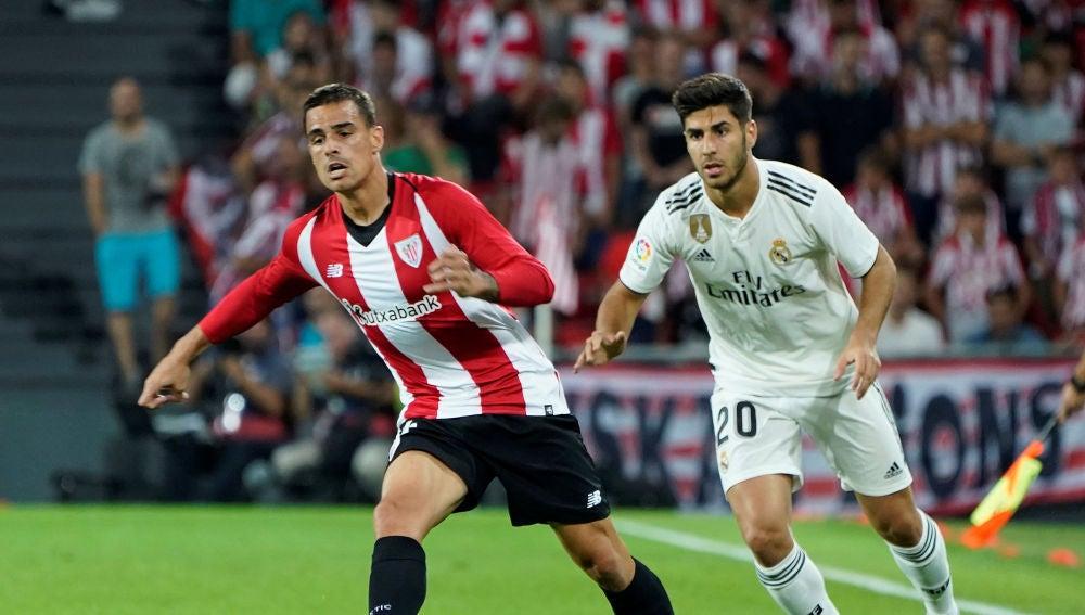 Dani García conduce el balón ante la presión de Marco Asensio