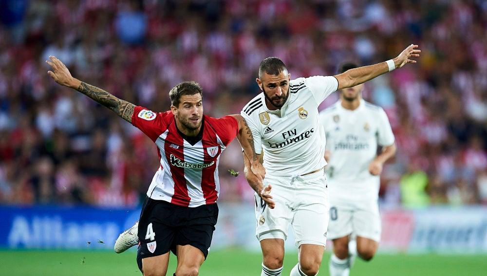 Iñigo Martínez y Benzema se disputan la posesión del balón