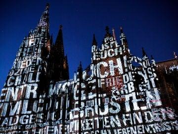 Fotografía donde se ve varios diseños proyectados sobre la fachada de la catedral de Colonia