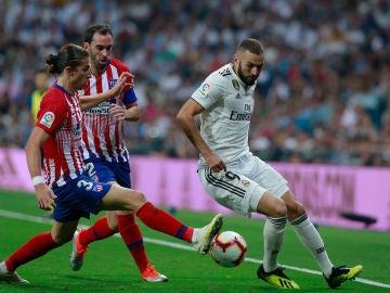 Benzema intenta zafarse de Filipe Luis y Godín