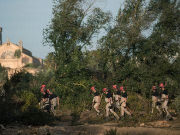 Buzos de la Guardia Civil y la Unidad Militar de Emergencias (UME) y agentes de diversos cuerpos a pie al niño