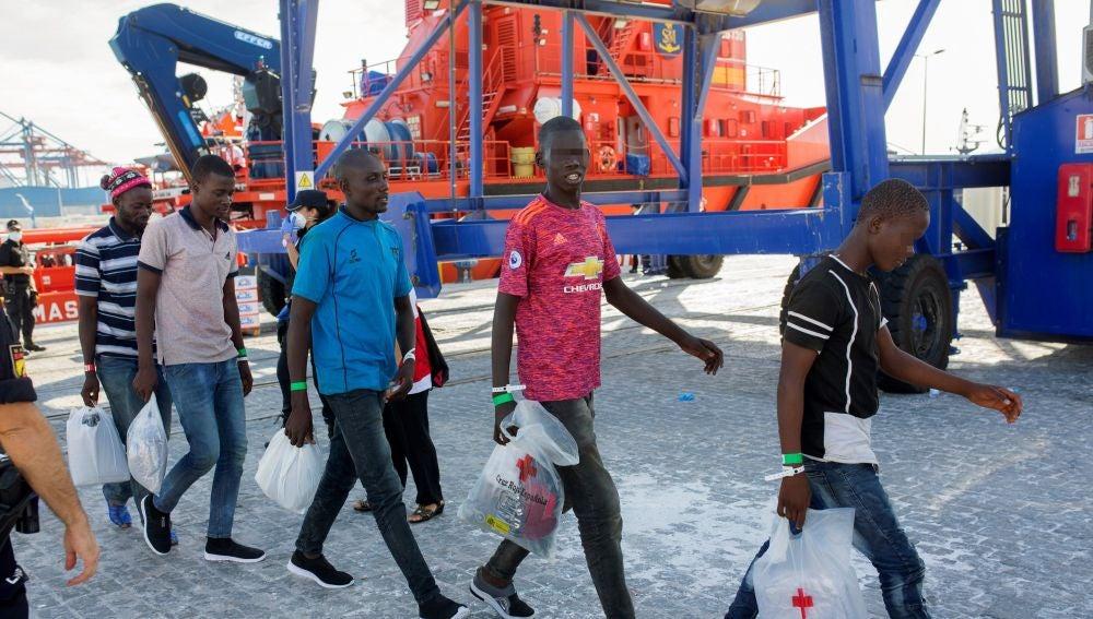 Varios inmigrantes salen de la embarcacíon para subir a un autobús que los llevará a San Roque