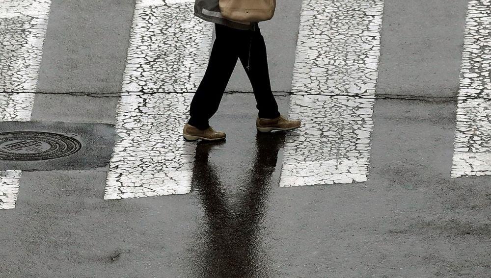 Una persona camina bajo la lluvia