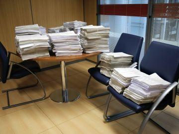 Imagen de varias reclamaciones apiladas en un despacho