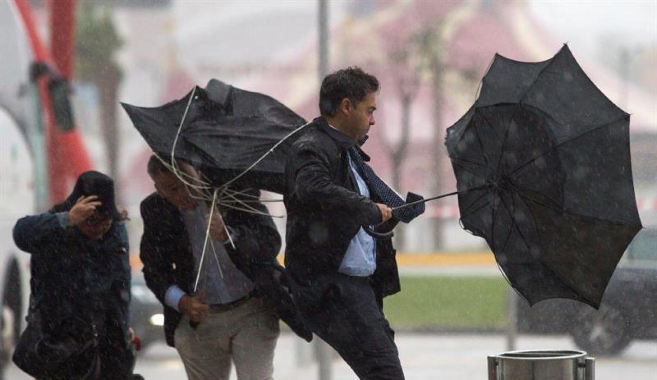 Varias personas sujetan sus paraguas por el fuerte viento
