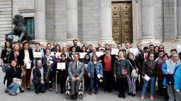 Miembros de diferentes colectivos a las puertas del Congreso de los Diputados