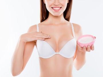 Mujer poniéndose crema en el pecho