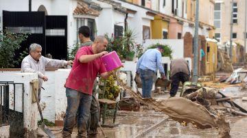 Un hombre limpiando los efectos de las lluvias