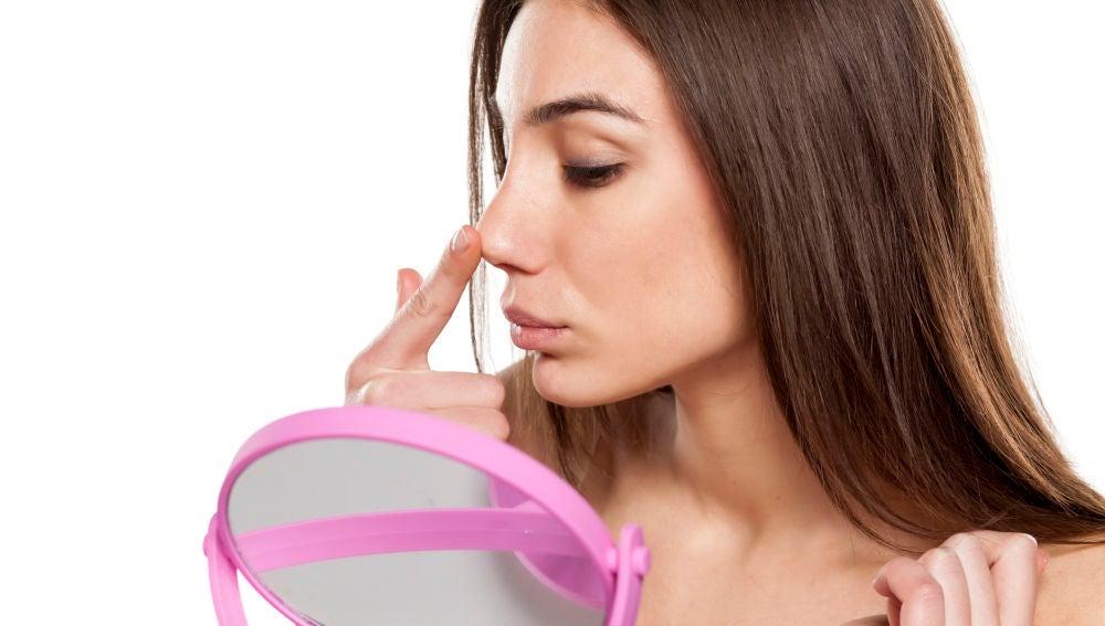 Mujer se mira la nariz frente al espejo
