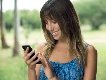 Una chica mirando su teléfono móvil