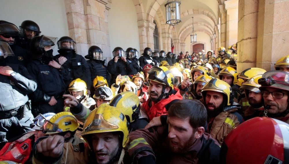 Mossos d'Esquadra tratan de impedir que decenas de bomberos entren en el edificio