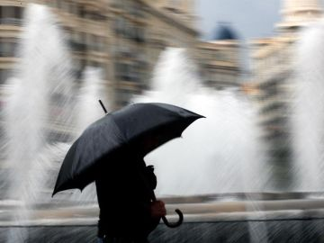 Una persona se resguarda de la lluvia con un paraguas en el centro de Valencia