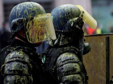 Agentes antidisturbios con los cascos manchados de pintura amarilla