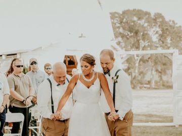 La joven caminando hacia el altar con su padre y su padrastro