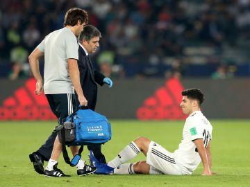 Asensio es atendido por los médicos durante el partido contra el Kashima