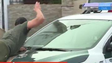 Un vecino sobre el coche de la Guardia Civil