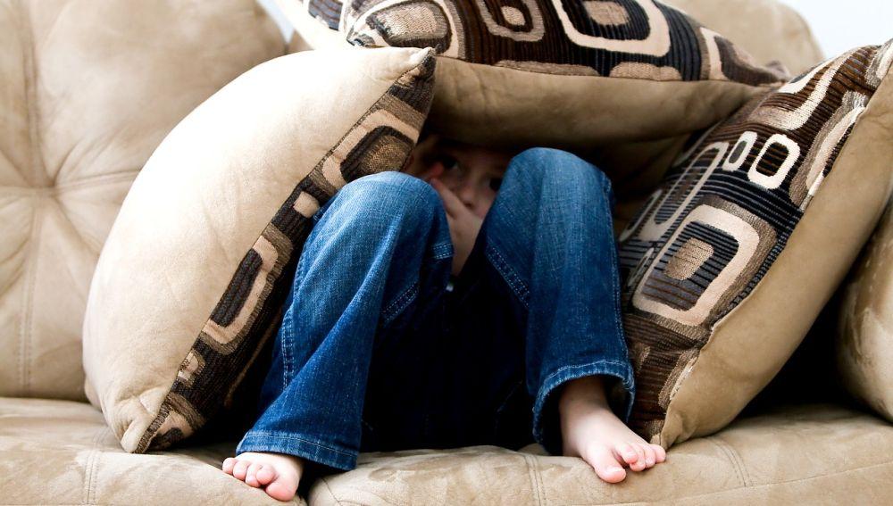 niño en un sofá con pies descalzos