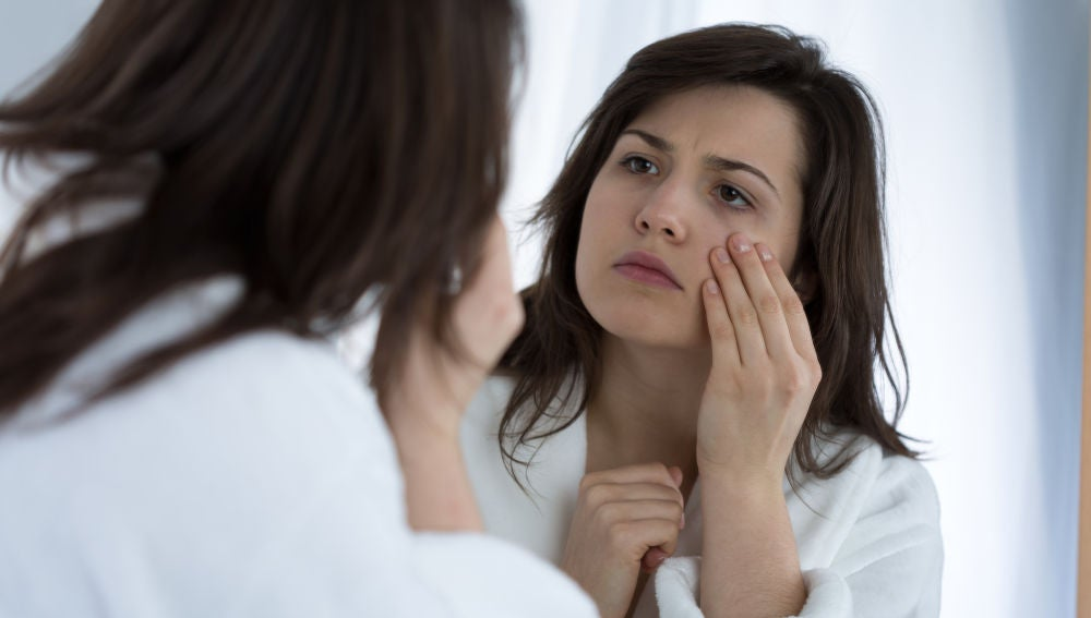 Mujer se mira los ojos frente al espejo