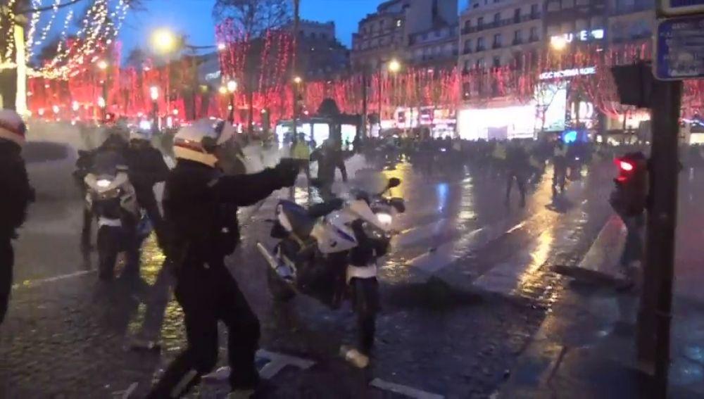 REEMPLAZO Un policía francés apunta con su arma a los 'chalecos amarillos' tras lanzar estos objetos contra los agentes y derribar la moto de uno de ellos