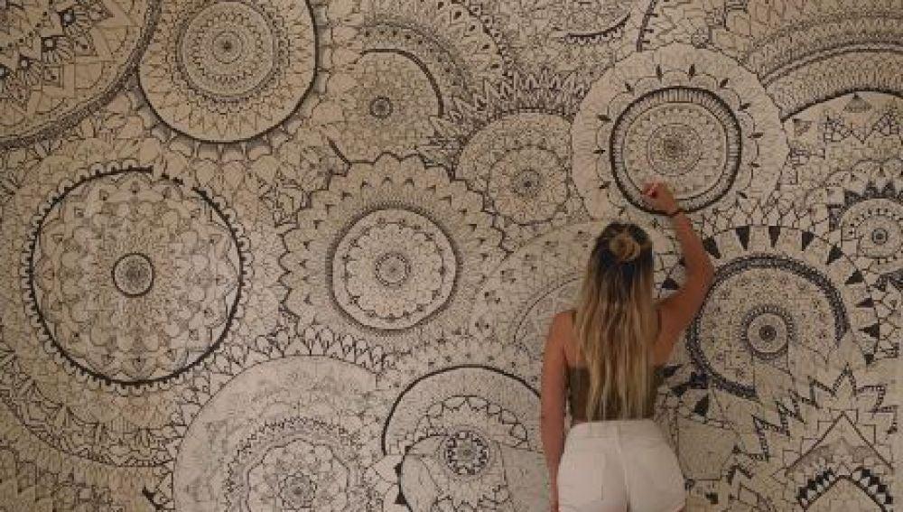 Una chica pinta mandalas en las paredes de su habitación