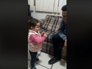 La pequeña intentando comunicarse con su padre