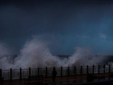 Una mujer es sorprendida por una ola en el Paseo Nuevo de San Sebastián