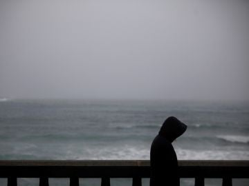Un hombre camina bajo la lluvia por el paseo marítimo de A Coruña