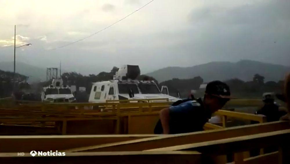 Tres miembros de la Guardia Nacional de Venezuela rompen con su tanqueta la barrera en la frontera con Colombia para desertar