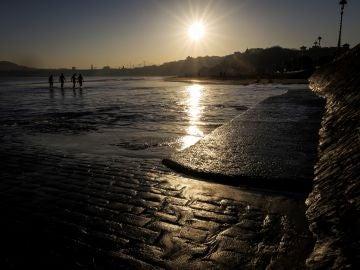 Varios hombres salen del agua al amanecer en la playa de Ondarreta de San Sebastián, donde este lunes los cielos se presentan despejados (25-02-2019)