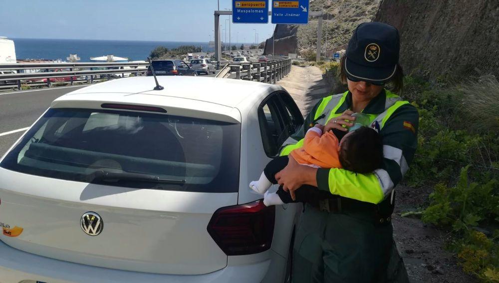 Agente de la Guardia Civil dando de comer a un bebé en la carretera